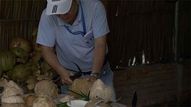 Le guide coupe une noix de coco